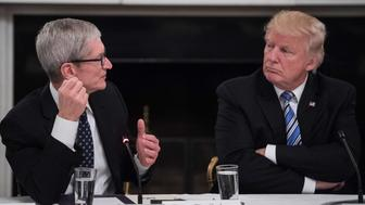 US President Donald Trump listens to Apple CEO Tim Cook speak during an American Technology Council roundtable at the White House in Washington, DC, on June 19, 2017. / AFP PHOTO / NICHOLAS KAMM        (Photo credit should read NICHOLAS KAMM/AFP/Getty Images)