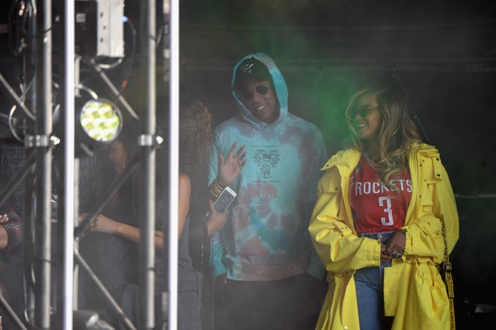 Jay-Z andBeyoncé watch a performance from the stage on Sunday.