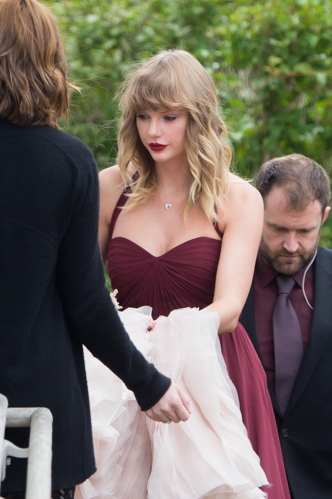 Taylor Swift is seen carrying the back of her BFF Abigail's wedding dress as they arrive at a church...
