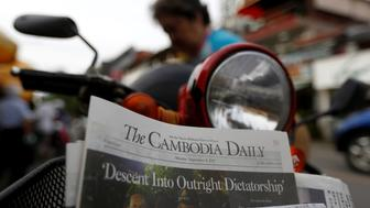 A woman buys the final issue of The Cambodia Daily newspaper at a store along a street in Phnom Penh, Cambodia, September 4, 2017. REUTERS/Samrang Pring
