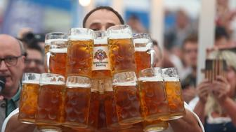 German Oliver Struempfel competes to set a new world record in carrying one liter beer mugs over a distance of 40 m (131 ft 3 in) in Abensberg, Germany September 3, 2017. Struempfel carried 27 mugs over 40 meters to set a new world record. REUTERS/Michael Dalder