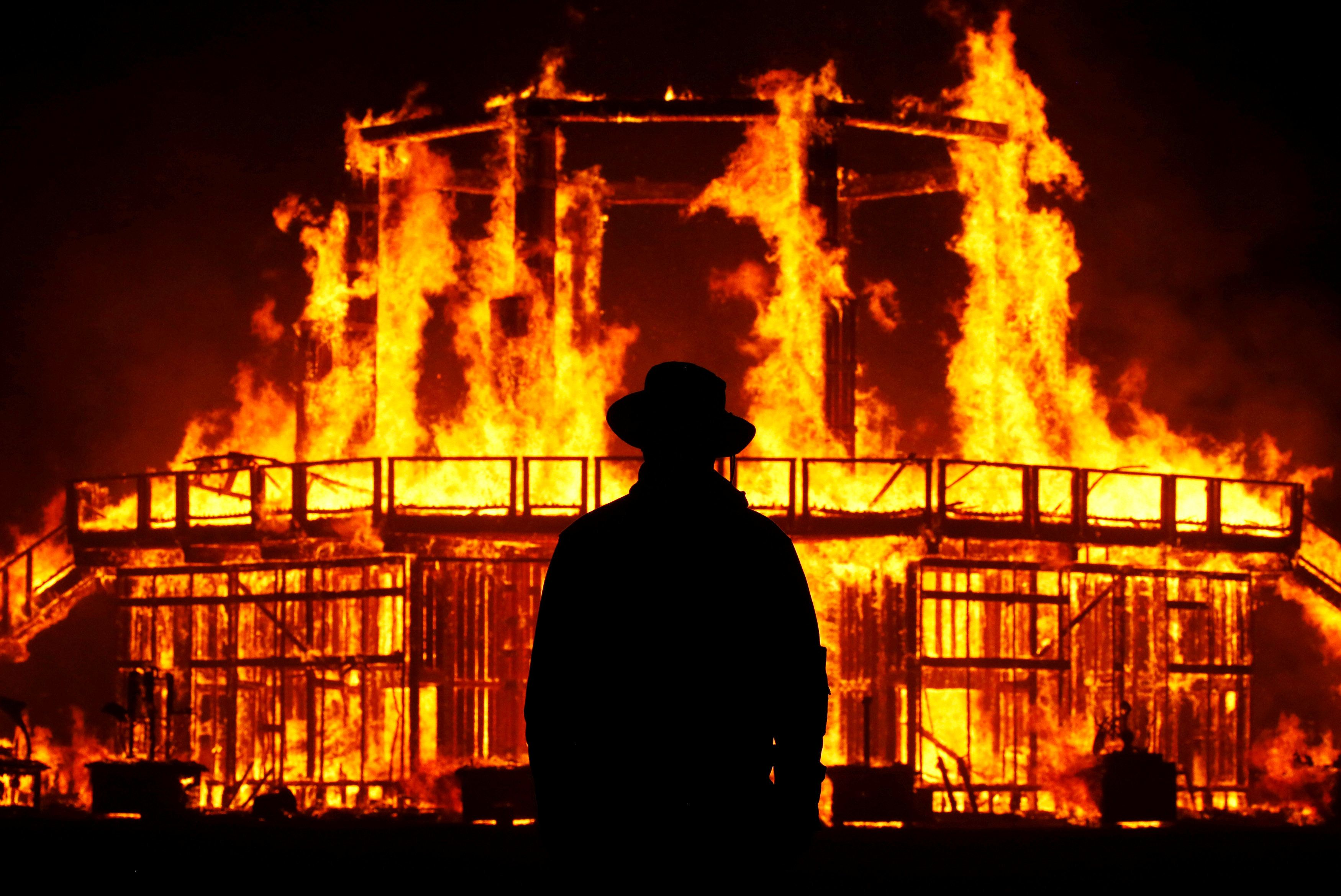 "A Burning Man Ranger guards the inner perimeter around the effigy of ""The Man"" as it burns at the culmination of the annual Burning Man arts and music festival in the Black Rock desert of Nevada, U.S. September 2, 2017. REUTERS/Jim Bourg   FOR USE WITH BURNING MAN RELATED REPORTING ONLY. FOR EDITORIAL USE ONLY. NOT FOR SALE FOR MARKETING OR ADVERTISING CAMPAIGNS. NO THIRD PARTY SALES. NOT FOR USE BY REUTERS THIRD PARTY DISTRIBUTORS"