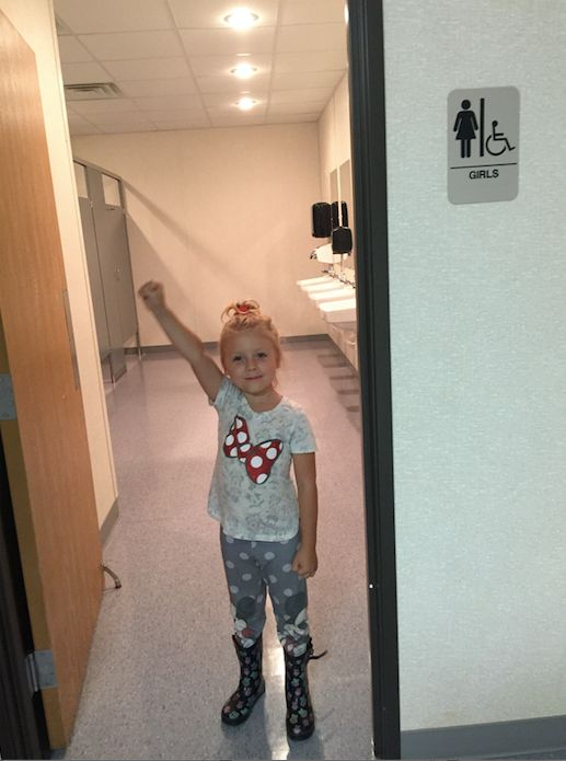 Emma raises a triumphant fist in the girls' bathroom at her new