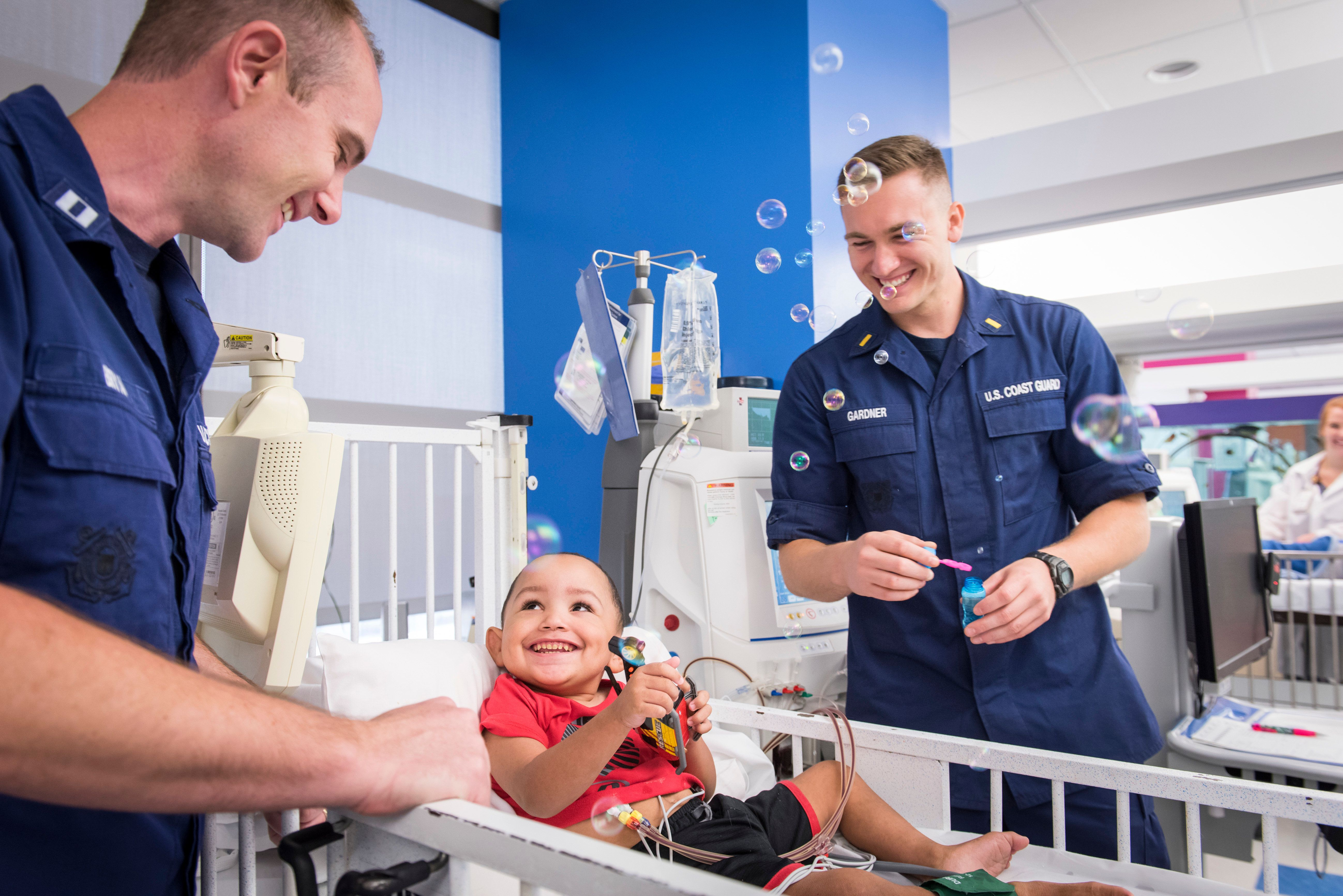 Coast Guard Lt. Brad Bryan (left) and Ensign James Gardner play with Zaiden Thomas, a dialysis patient who the two