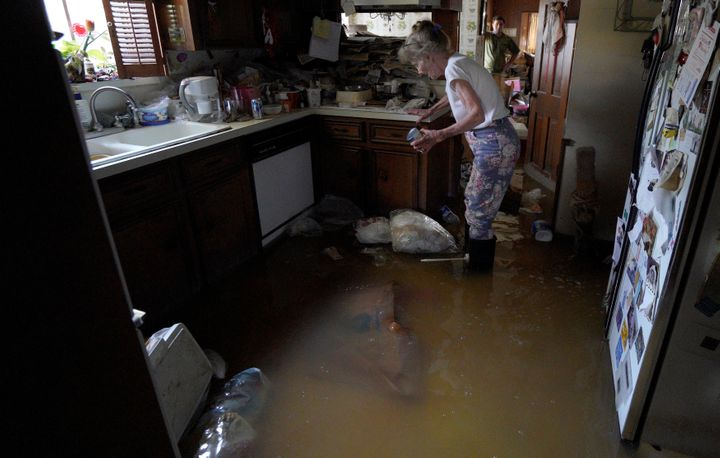 Nancy McBride collects items from her flooded kitchen as she returned to her home on Sept. 1, 2017, for the first time since