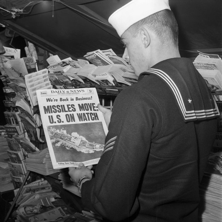 U.S. sailor reads the front page of the New York Daily News at a newsstand on November 9, 1962.