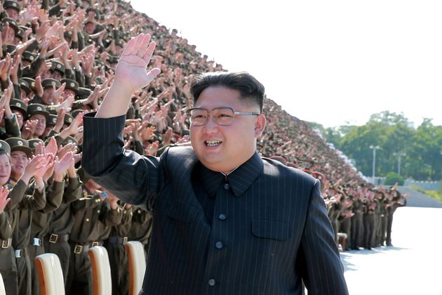 North Korean leader Kim Jong Un waves at a photo session with attendants in the fourth Active Secretaries...