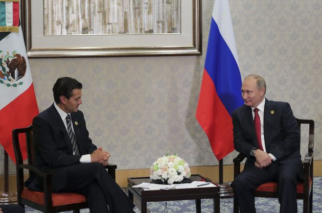 Russia's President Vladimir Putin (R) meets with Mexico's President Enrique Pena Nieto on the sidelines...
