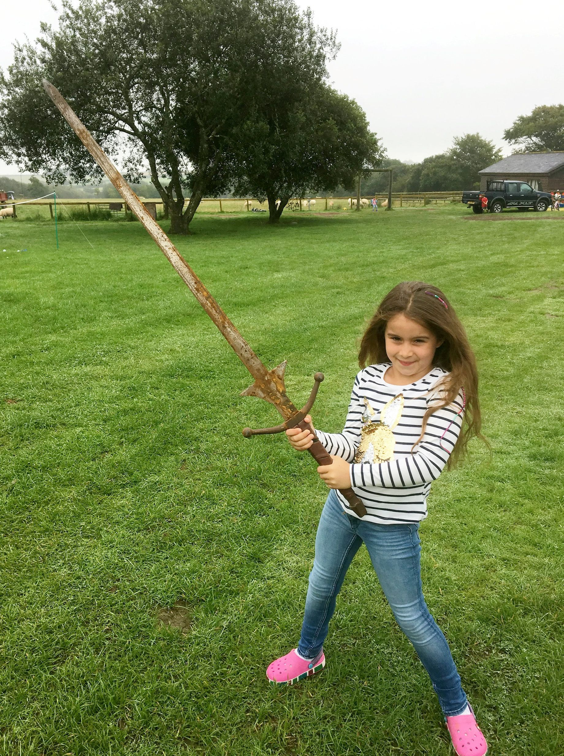 Matilda Jones, from Norton, Doncaster, with the sword.  A schoolgirl could become a thing of legend after pulling an historic sword from the same Cornish lake where King Arthur's Excalibur was famously thrown.  See ROSS PARRY story RPYSWORD.  Little Matilda Jones. Aged seven, came home with the perfect holiday souvenir after stumbling across the sword which is the same height as her.  She found the 4ft long metal blade while paddling in waist deep waters at Dozmary Pool on August 29.  Proud dad Paul Jones, 51, had only told Matilda and her sister Lois, four, about the legend of King Arthur moments before the discovery during a six-day holiday in Cornwall.  The 51-year-old, from Doncaster, south Yorks., predicts that the sword is probably around 30 years old and was used as an old film prop.