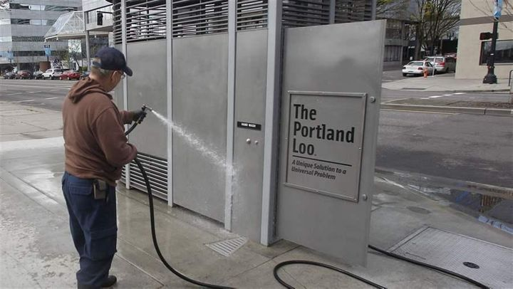 A man hoses down a Portland Loo in Portland, Oregon.