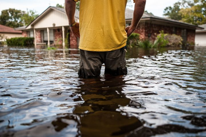 "Oden ""Odie"" Walder walks up to his flooded home in Angleton, Texas, on Monday."