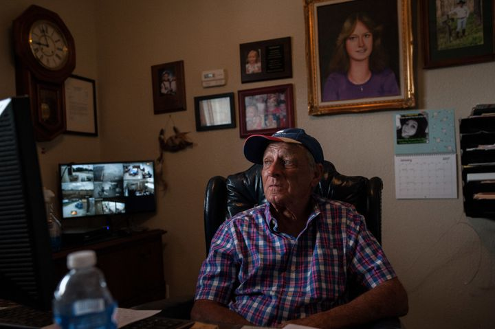 Tim Miller sits in his office in front of a portrait of his daughter, Laura. Miller founded EquuSearch in 2000 in honor of La