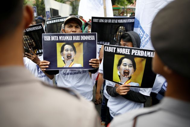 Protesters outside of Myanmar's embassy in Jakarta hold signs protesting Myanmar's government and Aung...