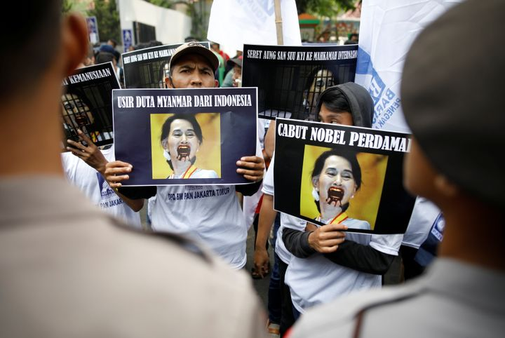 Protesters outside of Myanmar's embassy in Jakarta hold signs protesting Myanmar's government and Aung San Suu Kyi on Sept. 4
