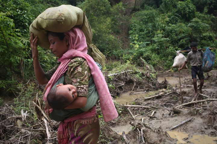 A Rohingya woman carries her child in a sling after crossing the border into Bangladesh on Sept. 5, 2017.