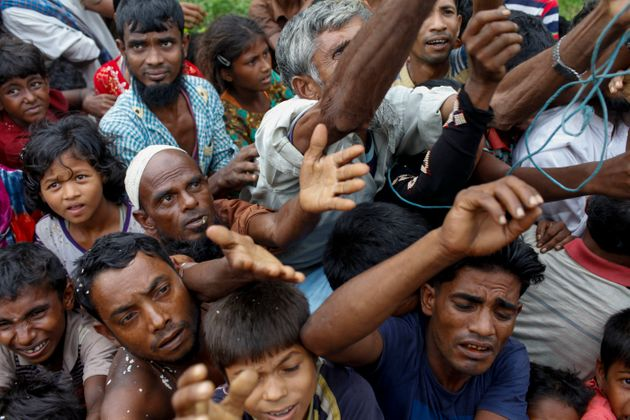 Rohingya refugees wait for aid at Kutupalong refugee camp in the town of Teknaf, Bangladesh, on Sept....