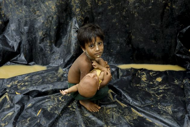 A Rohingya child holds a baby after arriving at a refugee camp near Teknaf, Bangladesh, on Sept. 5,