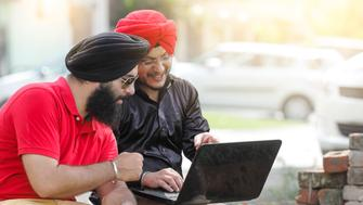 Two Sikh men using laptop in the park