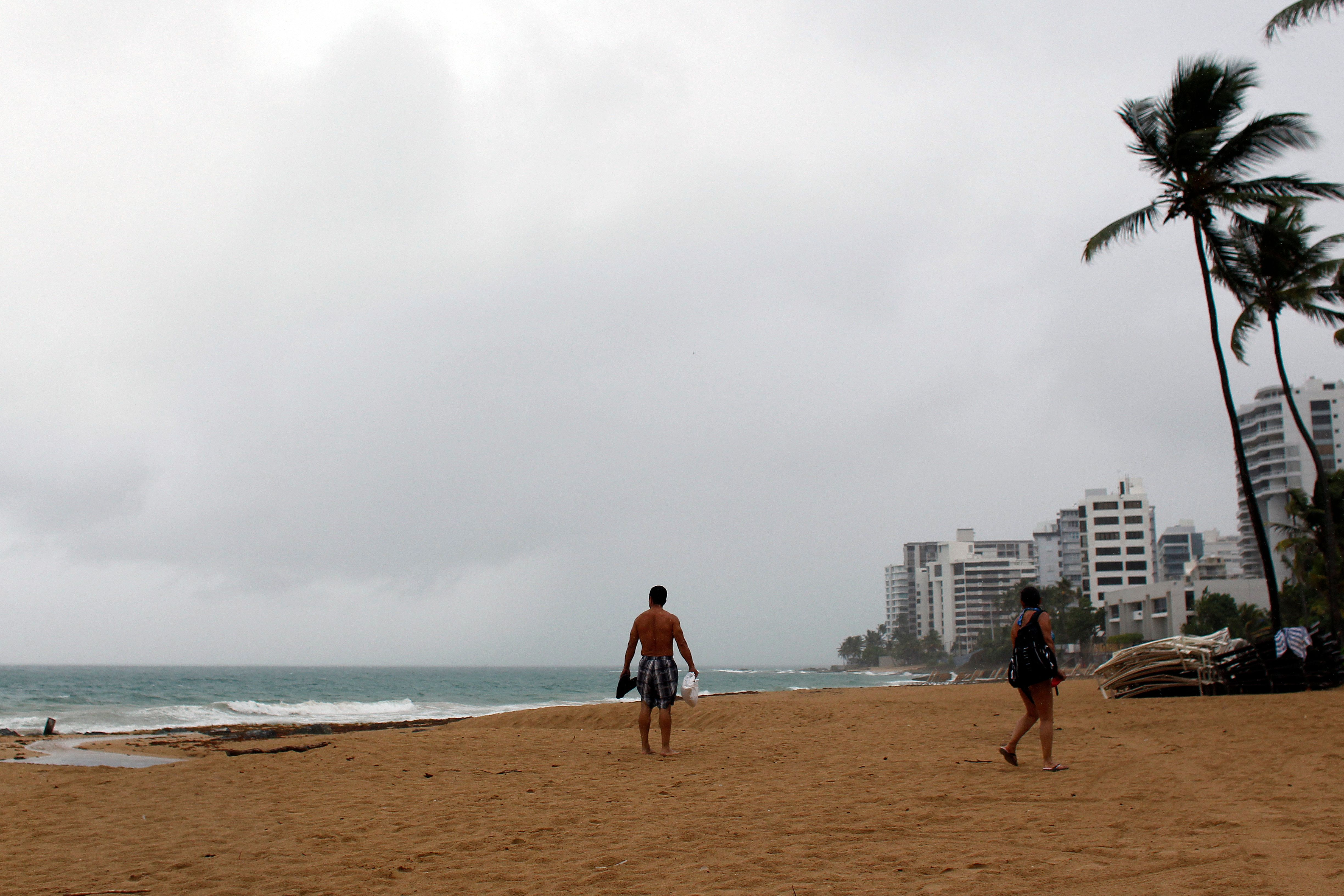 A couple walks on a beach as hurricane Irma approaches Puerto Rico in San Juan, on September 5, 2017. In Puerto Rico, a US territory of 3.5 million, Governor Ricardo Rossello activated the National Guard and announced the opening of storm shelters able to house up to 62,000 people. The major of the Puerto Rican capital San Juan, Carmen Yulin Cruz Soto, ordered 900 municipal employees -- police, emergency personnel, and aid and social workers -- to report for rotating 12-hour shifts.Even if Puerto Rico is spared a direct hit, the mayor said, three days of pounding rain will do heavy damage.  / AFP PHOTO / Ricardo ARDUENGO        (Photo credit should read RICARDO ARDUENGO/AFP/Getty Images)