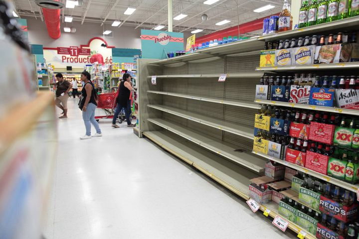 Customers in San Juan walk near empty shelves that are normally filled with bottles of water after Puerto Rico Gov. Rica
