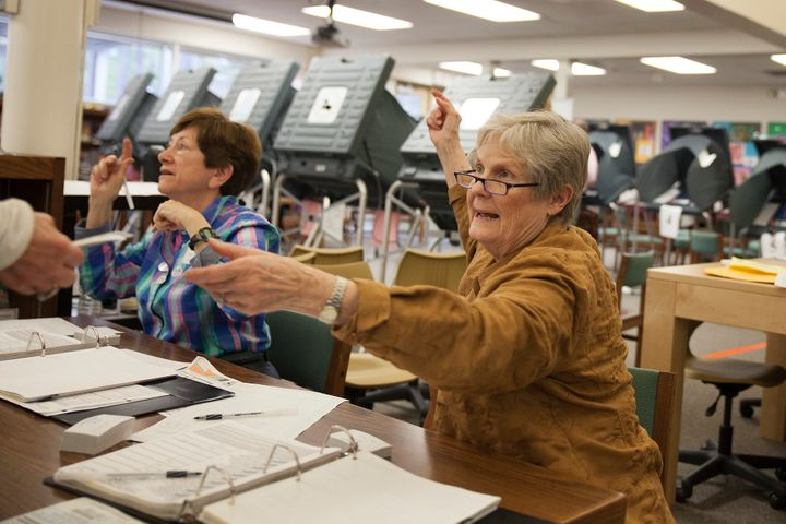 Ann Moss checks a voter's ID in Houston. Texas' voter ID law is considered one of the strictest in the U.S.