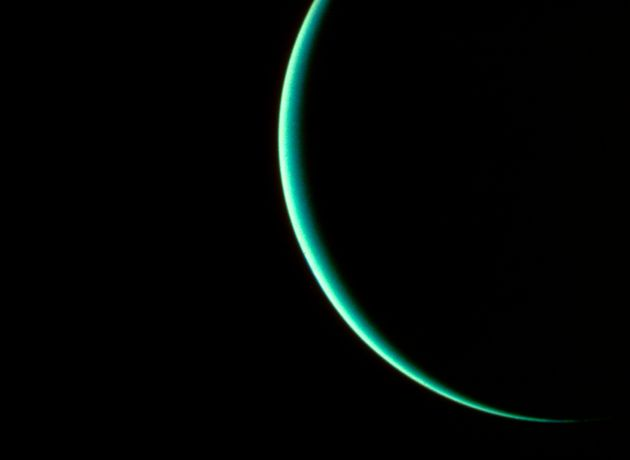 The planet Uranus, obscured except for a thin crescent, photographed by interplanetary probe Voyager...