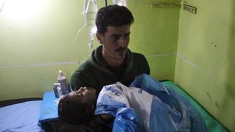 TOPSHOT - An unconscious Syrian child is carried at a hospital in Khan Sheikhun, a rebel-held town in the northwestern Syrian Idlib province, following a suspected toxic gas attack on April 4, 2017.  A suspected chemical attack killed at least 58 civilians including several children in rebel-held northwestern Syria, a monitor said, with the opposition accusing the government and demanding a UN investigation. / AFP PHOTO / Omar haj kadour        (Photo credit should read OMAR HAJ KADOUR/AFP/Getty Images)