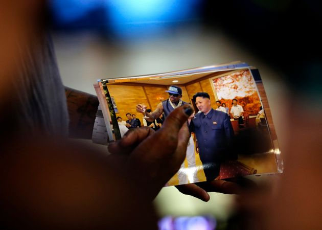 <strong>Rodman shows a picture which he took with North Korean leader Kim Jong-un as he arrives...