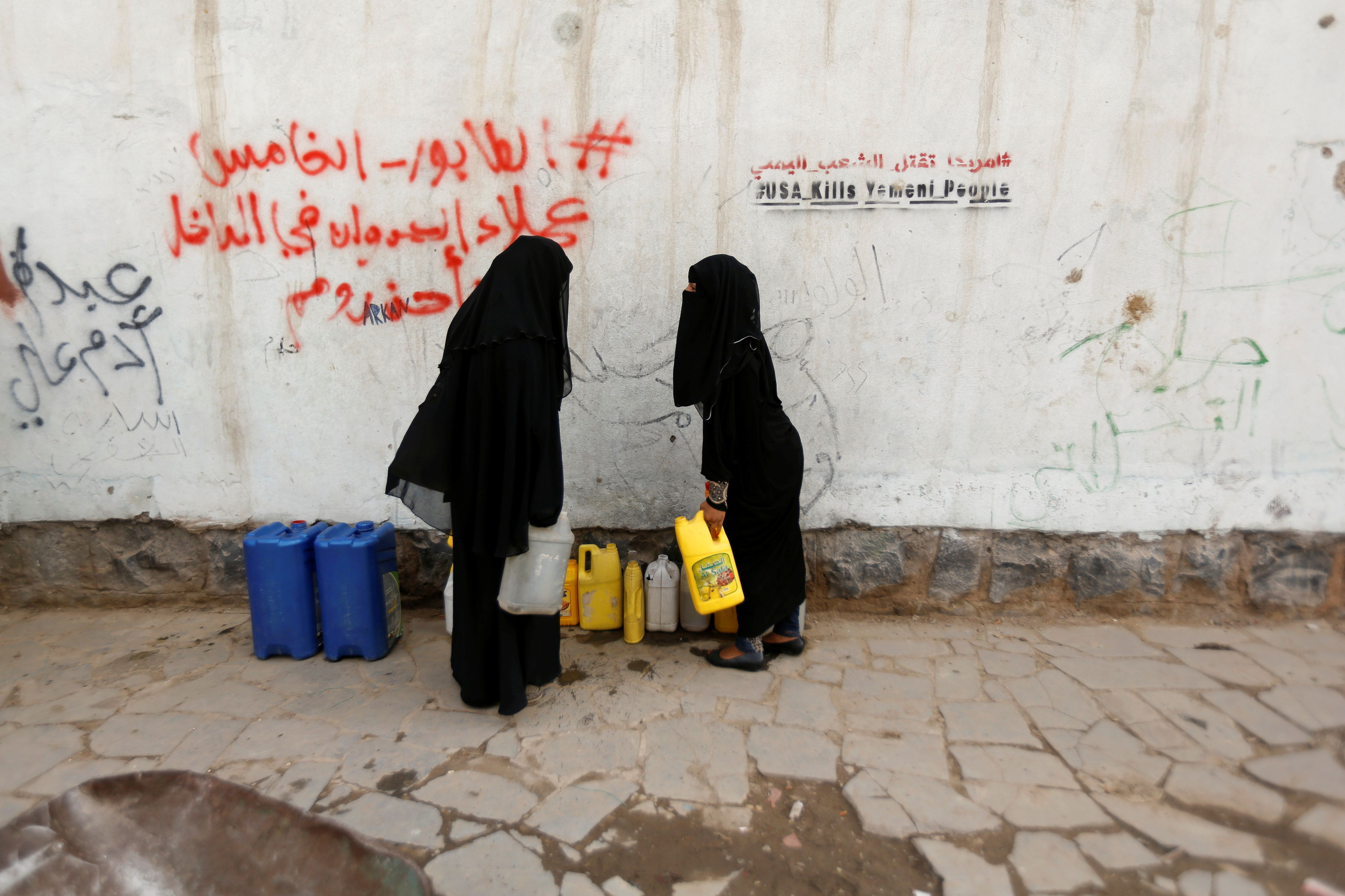 """Women carry jerrycans after they filled them up with drinking water from a charity tap, amid a cholera outbreak, in Sanaa, Yemen, July 10, 2017. REUTERS/Khaled Abdullah        SEARCH """"CHOLERA KHALED"""" FOR THIS STORY. SEARCH """"WIDER IMAGE"""" FOR ALL STORIES."""