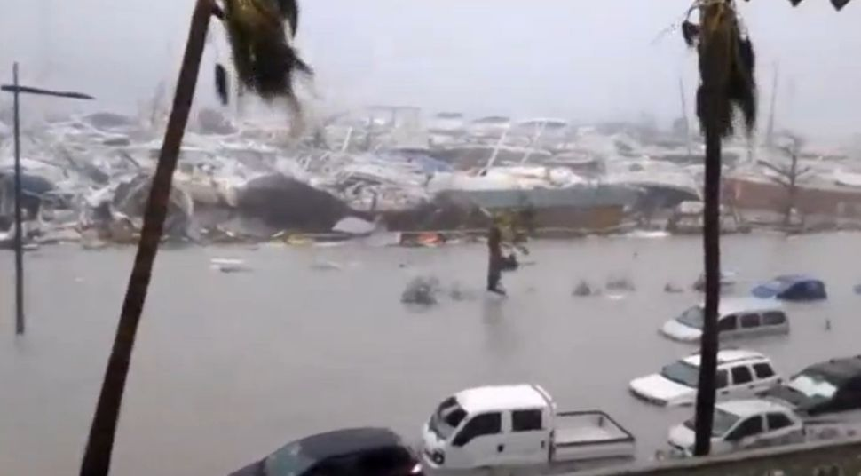 Half-submerged cars, trucks, boats and debris in the flooded harbor as Hurricane Irma hits the French island territory of Sai