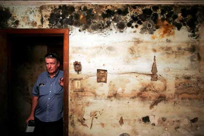 Two years after Hurricane Katrina, a New Orleans resident poses in his mold-infested home.