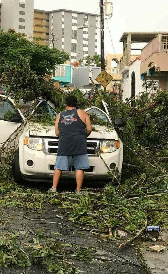 A man removes debris from a car as Hurricane Irma nears San Juan, Puerto Rico, on Sept. 6, 2017.