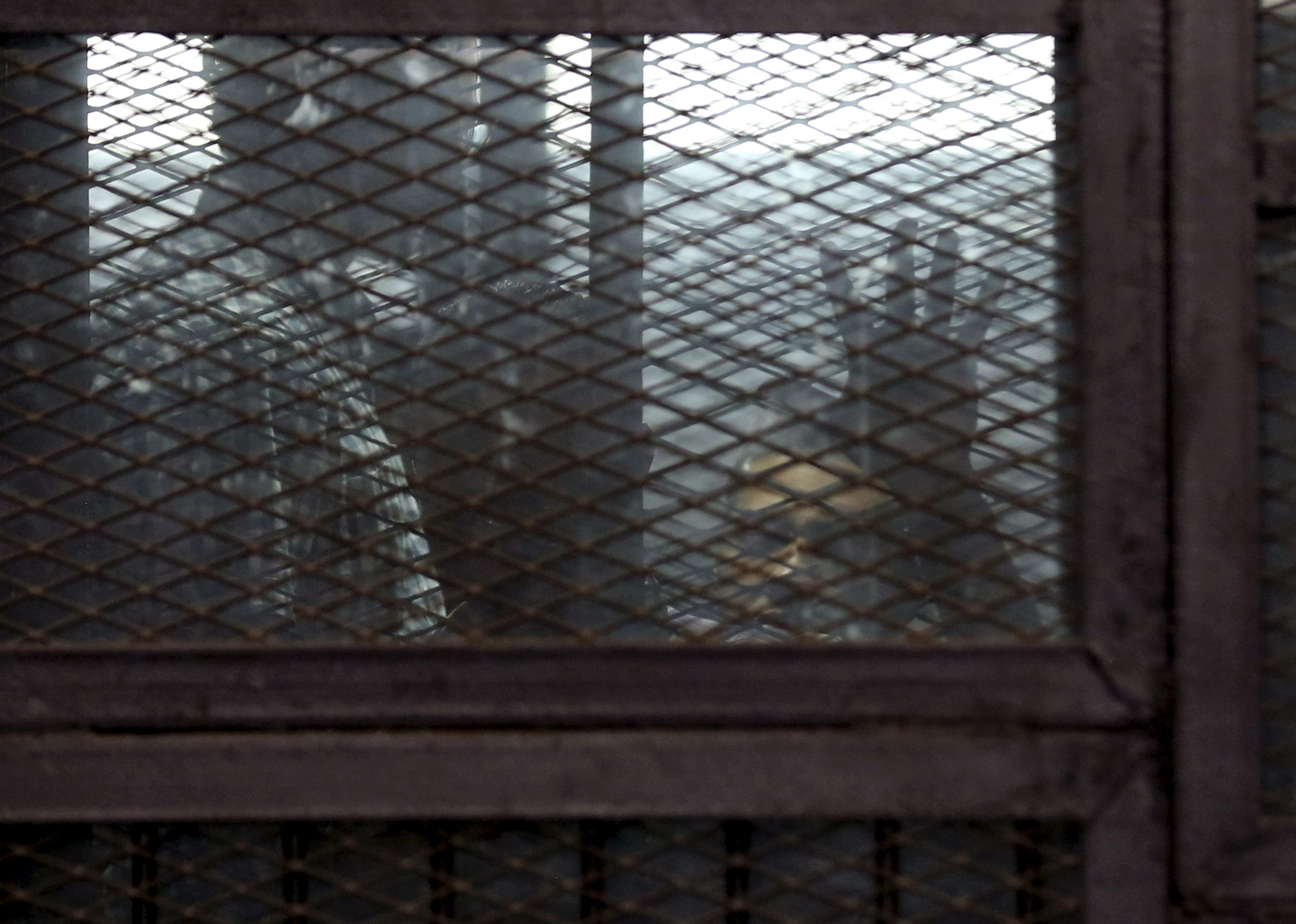 Al Jazeera television journalists Mohamed Fahmy and  Baher Mohamed are seen behind bars before hearing the verdict at a court in Cairo, Egypt, August 29, 2015. An Egyptian court sentenced three Al Jazeera TV journalists to three years in prison on Saturday for operating without a press licence and broadcasting material harmful to Egypt, a case that has triggered an international outcry. The verdict in a retrial was issued against Mohamed Fahmy, a naturalised Canadian who has given up his Egyptian citizenship, Baher Mohamed, an Egyptian, and Peter Greste, an Australian who was deported in February. REUTERS/Asmaa Waguih