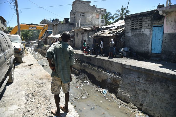 A man watches while a bulldozer clean debris in a canal, in Cap-Haitien, on September 6, 2017, 240 km from Port-au-Prince, in