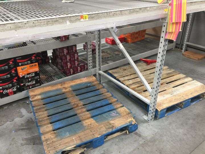 Wooden pallets and shelves that used to hold stacks of bottled water are empty at a Walmart in Fort Lauderdale on Wednesday.