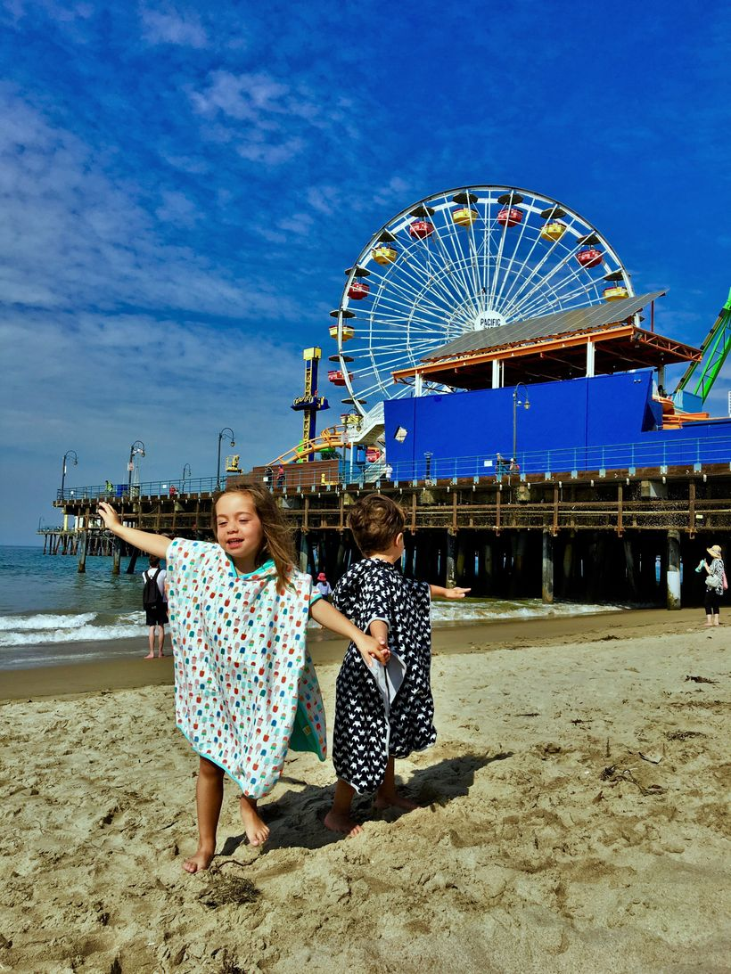 London and Miles enjoying the Santa Monica pier in their ponchos that work in summer or #endless-summer adventures!  With a s