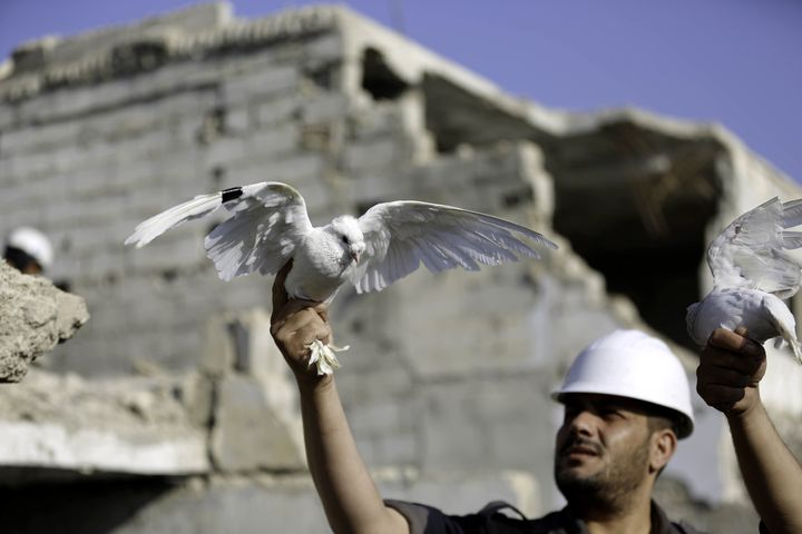 A member of the White Helmets let a white pigeon fly for people who lost his life in a chemical attack in the Eastern Gh