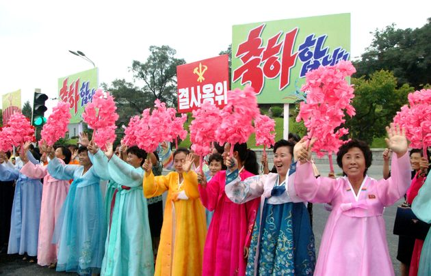 North Koreans cheer as members who worked on the test arrive in
