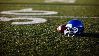 An American football helmet and football on the football field. Perfect image for your football announcement.