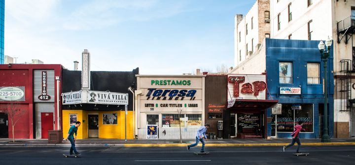UNITED STATES - FEBRUARY 22: Skateboarders zip past a colorful row of small businesses in downtown El Paso, Texas (Photo by C