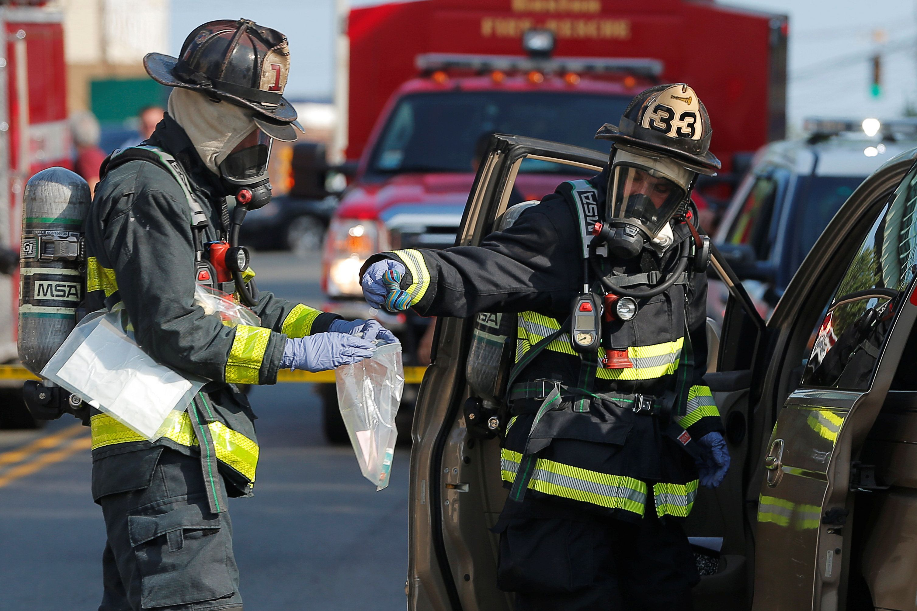Firefighters in hazmat protection remove items from a vehicle in which several drug overdose victims were found, in addition to a powder believed to be fentanyl, in Chelsea, Massachusetts, U.S., August 4, 2017. REUTERS/Brian Snyder