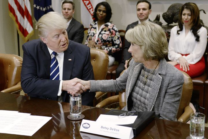 President Donald Trump shakes hands with Betsy DeVos during a parent-teacher conference listening session inside the Roosevel