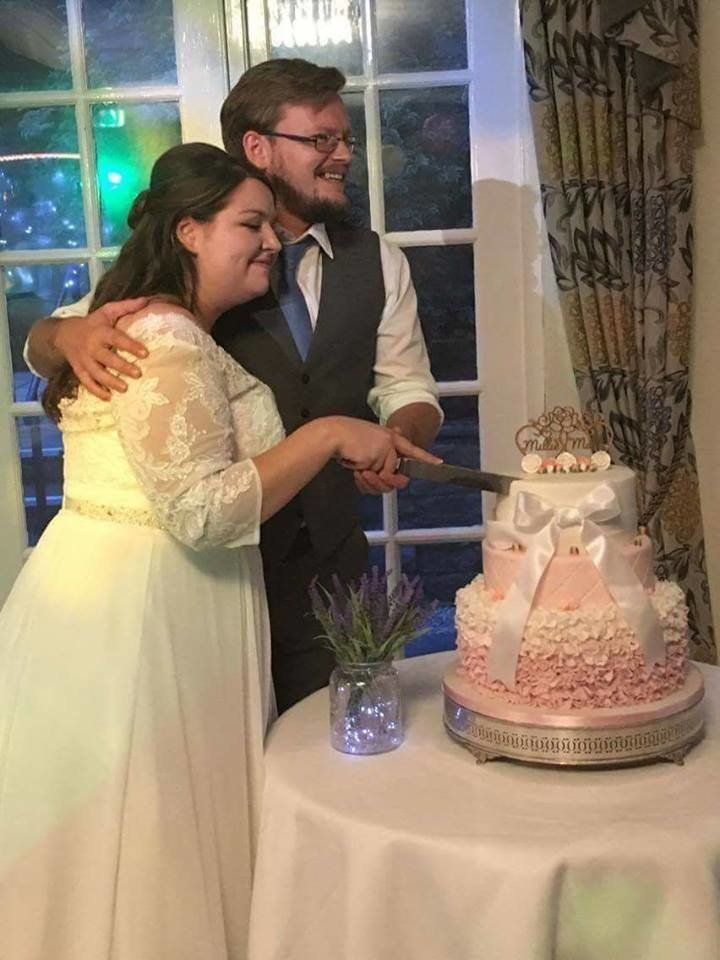 The newlyweds cutting the repaired cake.