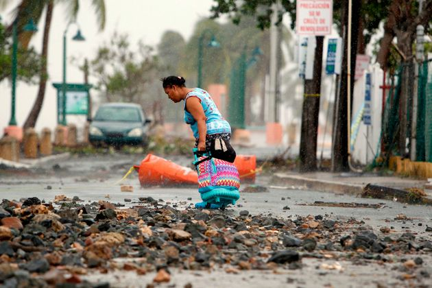 A woman pulls a suitcase along on a rock-strewn road in the aftermath of Hurricane Irma in Fajardo, Puerto...