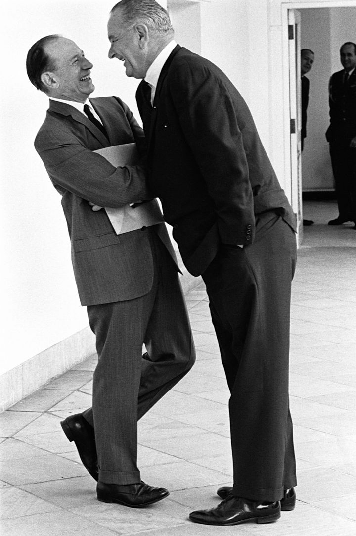 President Lyndon B. Johnson leans over a political colleague in mock intimidation to parody how he gets his way in Washington