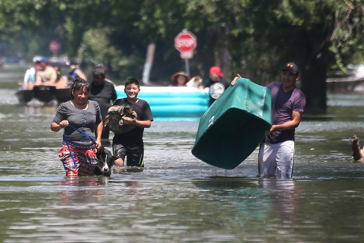 People walk with their possessions out of a flooded area of Port Arthur, Texas on Aug.31, 2017.