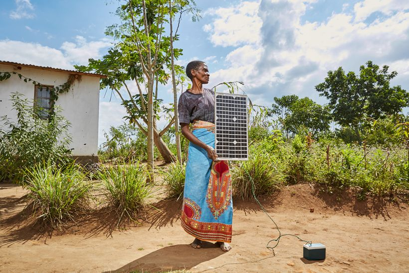 Violet Napazi, 57, holds up the solar panel owned by her son, Master, Luchenza, southern Malawi, 2017. Charging mobile phones