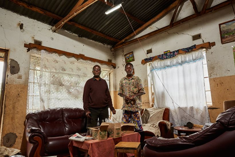 Robert Wonga (56), and his son Felix (29) stand in the living room of their home, Luchenza, southern Malawi, 2017. The solar