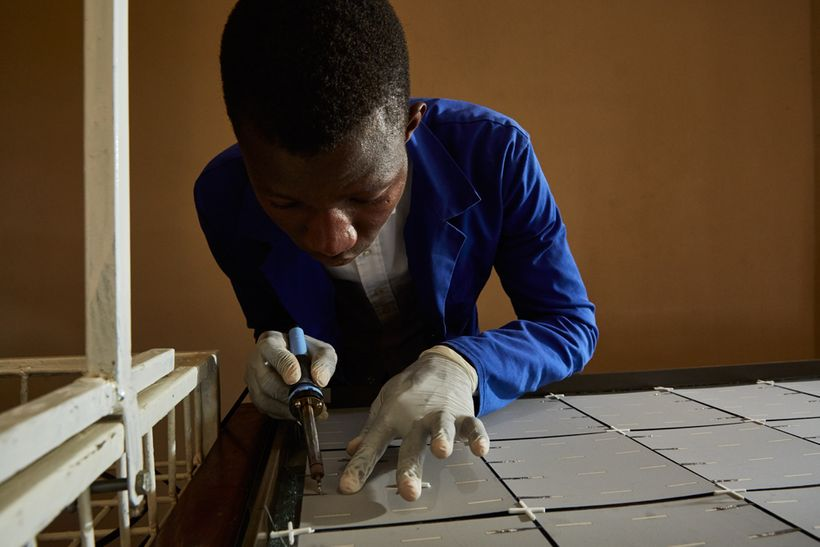 Thomas, a student at Green Malata, an entrepreneurial village, carefully solders metal strips to the back of a solar panel, L