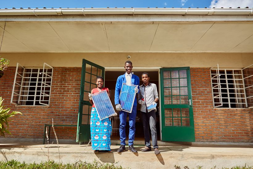From left to right: Jennifer, Thomas, and Alex, students at Green Malata, an entrepreneurial village, pose with some of their